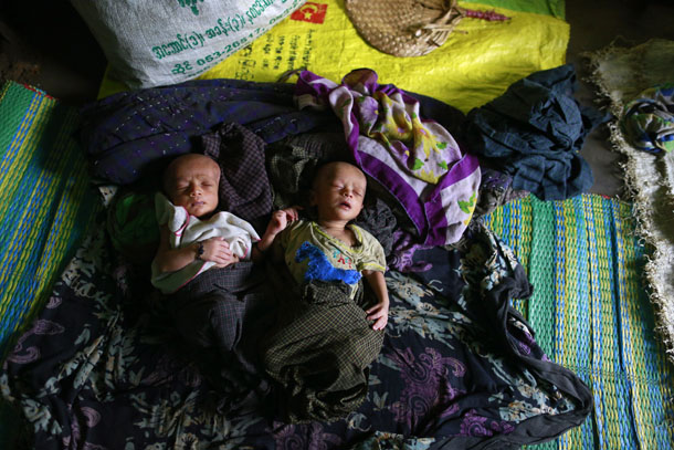 Twin Rohingya babies sleep inside a hut at a refugee camp outside Sittwe, the capital city of Arakan State, on June 9, 2014. (Photo: Reuters / Soe Zeya Tun)
