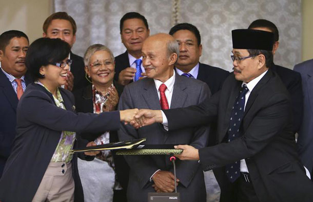 Government of the Philippines chief negotiator Miriam Coronel Ferer shakes hands with Moro Islamic Liberation Front chief negotiator Mohagher Iqbal, right, as they exchange peace agreements in Kuala Lumpur on Jan. 25, 2014. (Photo: Reuters)