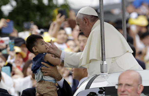 Pope Francis blesses a child as he arrives for a closing Holy Mass of the 6th Asian Youth Day in Haemi Castle in Haemi, south of Seoul, on August 17, 2014. (Photo: Reuters)