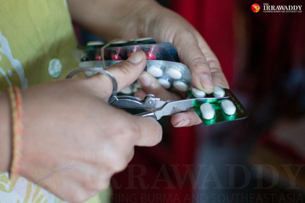 A drugstore employee prepares medicine for a customer in Rangoon. (Photo: Sai Zaw / The Irrawaddy)