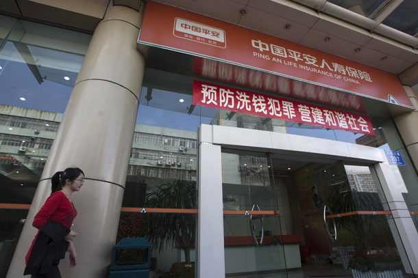 A woman walks past a Ping An Insurance building in Shenzhen on Feb. 5, 2013. (Photo: Reuters / Tyrone Siu)
