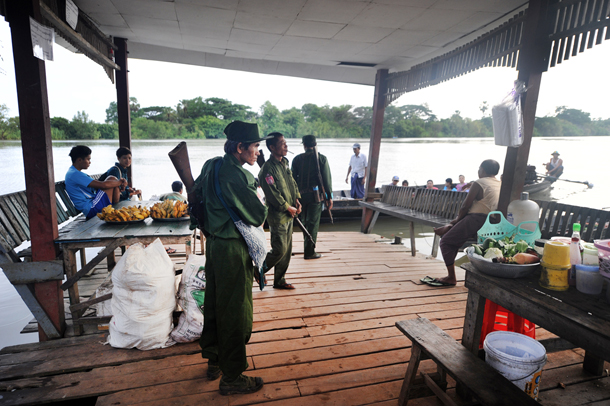 Soldiers from the Burmese Army check identity cards at a jetty for those entering and exiting Kyaikmayaw Township in Mon State by boat on Monday. (Photo: Steve Tickner / The Irrawaddy)