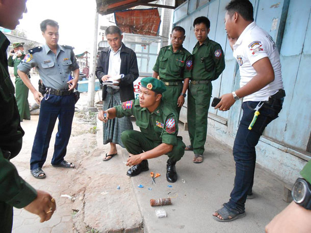 Authorities in Myawaddy Township gather around an explosive device discovered in the border town on Tuesday morning. (Photo: Karen National Media)