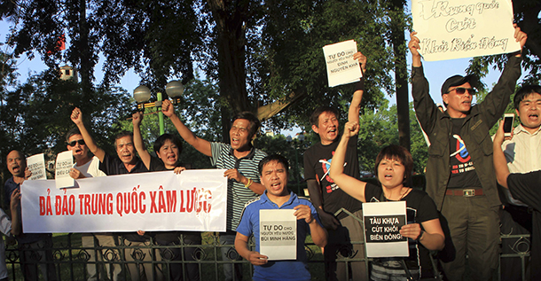 "Protesters shout as they hold an anti-China banner which reads, ""down with China"" at a park in front of the Chinese Embassy in Hanoi on May 9, 2014."