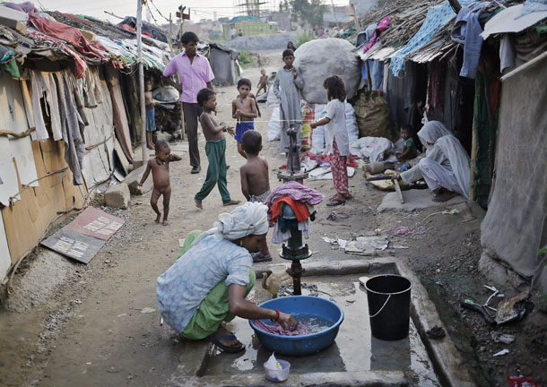 A woman, who says she belongs to the Rohingya community from Burma, washes clothes as children play in a camp in New Delhi on September 13, 2014. (Photo: Reuters).