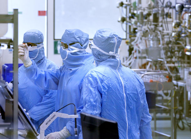 Employees work in the cell culture unit at the French