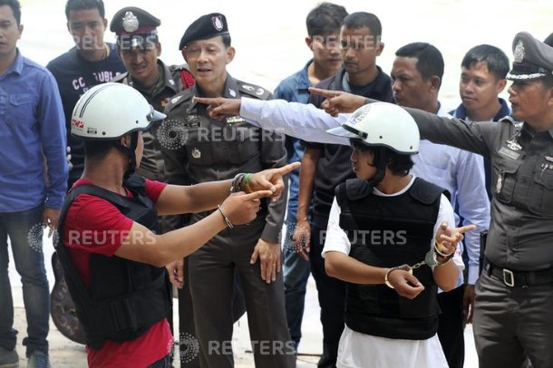 Two Burmese migrant workers suspected of killing two British tourists on Koh Tao last month stand with Thai police officers during a re-enactment of the alleged crime. (Photo: Reuters)