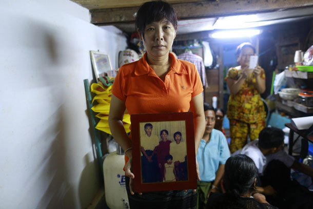 Thandar, the widow of slain journalist Par Gyi, holds a family photograph in Rangoon on Oct. 28, 2014, showing herself, her husband and daughter posing with Aung San Suu Kyi at their home. (Photo: Reuters / Soe Zeya Tun)