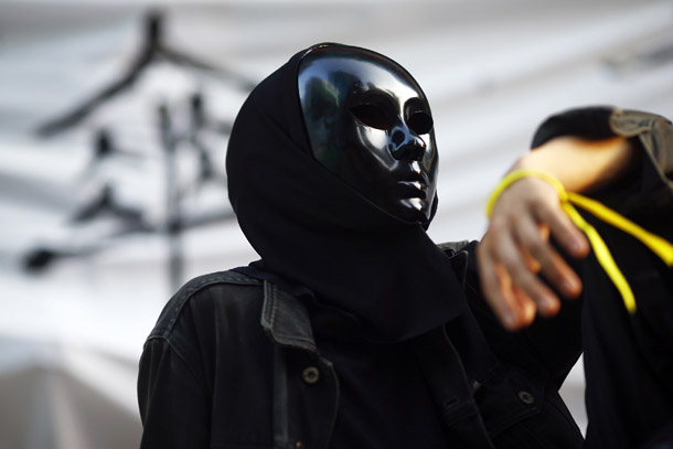 A pro-democracy protester wears a mask as he monitors barricades set-up in Mongkok shopping district in Hong Kong October 30, 2014. (Photo: Reuters)