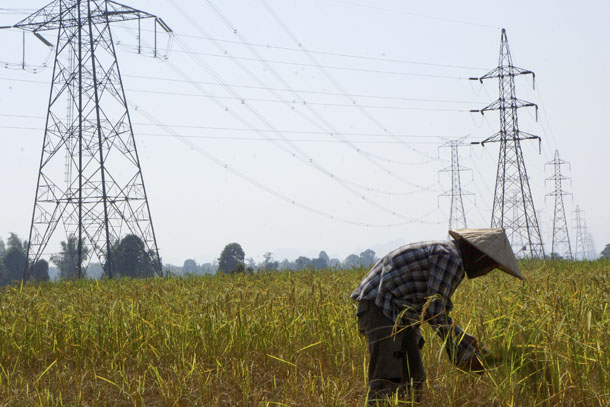 A farmer works in a paddy field under the power lines near Nam Theun 2 dam in the Laotian province of Khammouane on Oct. 28, 2013. (Photo: Reuters)
