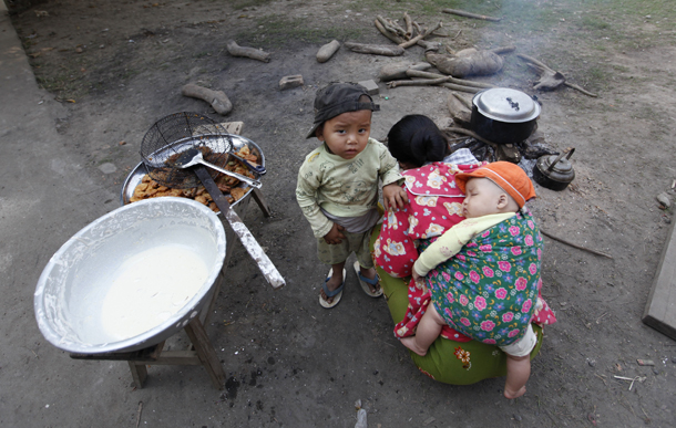 A woman stokes a cooking fire with her two children at a camp for displaced people near Myitkyina, Kachin State in 2012. (Photo: Reuters)
