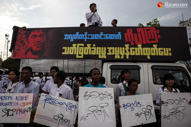 Demonstrators gather behind a banner in downtown Rangoon on Sunday, Oct. 26, 2014. (Photo: JPaing / The Irrawaddy)