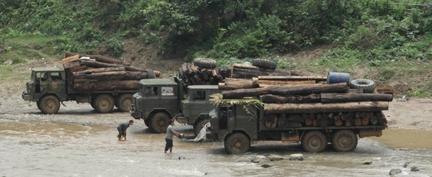 Trucks loaded with Burmese timber wait to cross a river on the Burma-China border. (Photo: EIA)