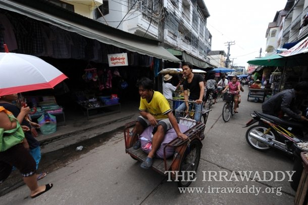 Burmese workers transporting goods are seen inside the main market in Mae Sot, in Thailand's Tak Province. (Photo: Steve Tickner / The Irrawaddy)