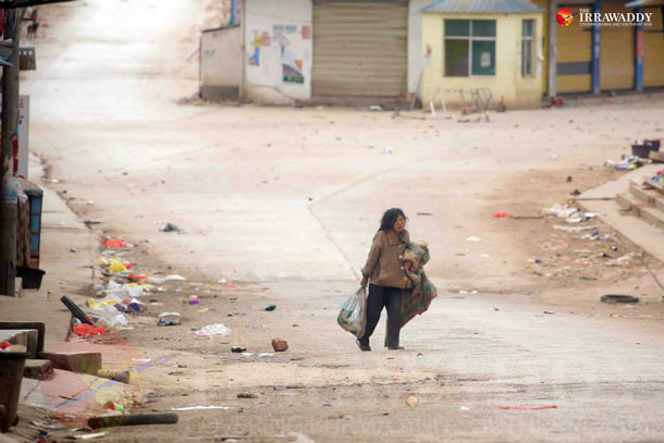 A woman walks with her belongings down an otherwise deserted street in Laukkai earlier this month. (Photo: JPaing / The Irrawaddy)