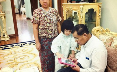 Retired Sen-Gen. Than Shwe is seen receiving instructions on how to use an iPad from his granddaughter in this photo shared on Facebook by his grandson. (Photo: Nay Shwe Thway Aung /Facebook)