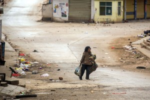 A lone woman carries her possessions through the deserted streets of Laukkai in mid-February after clashed broke out in the area between the MNDAA and the Myanmar Army.