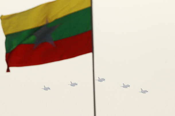 Fighter jets are seen behind Burma's flag during a parade to mark Armed Forces Day in the capital Naypyidaw on March 27, 2013. (Photo: Reuters)