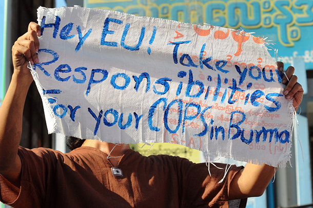 A demonstrator holds a sign protesting the European Union's police training program on Friday in Rangoon. (Photo: Steve Tickner / The Irrawaddy)