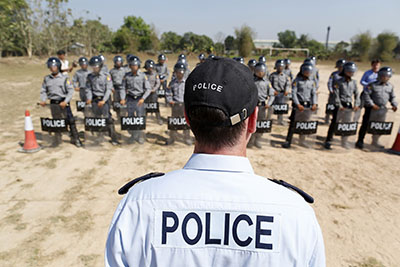 A trainer from the European Union stands in front of riot policemen during a training session under the EU's programme to support reform of the Burmese Police Force at a police training camp outside Rangoon, February 20, 2014. (Photo: Reuters)