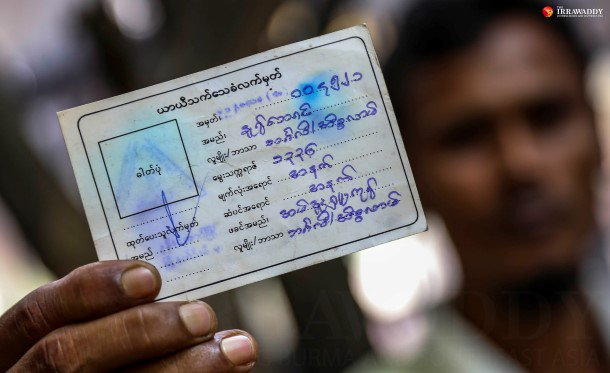 "A man identified as an ethnic Bengali holds up his temporary identity ""white card."" (Photo: JPaing / The Irrawaddy)"