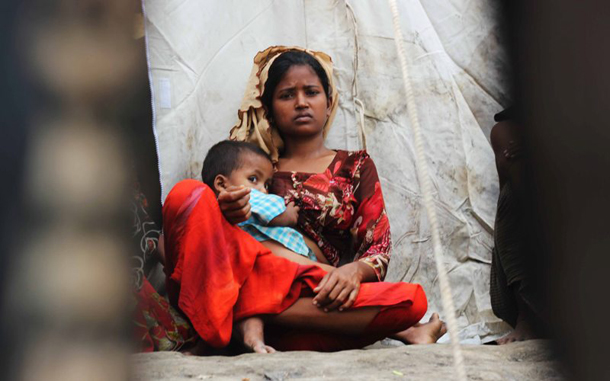 A displaced Rohingya woman sits with her child outside a temporary camp in Pauktaw Township, Arakan State. (Photo: The Irrawaddy)