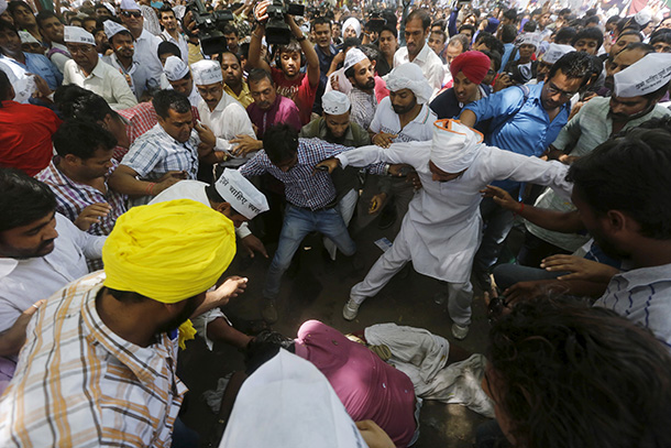 Protesters gather around a farmer who hung himself from a tree during a rally in New Delhi on Wednesday. (Photo: Adnan Abidi / Reuters)