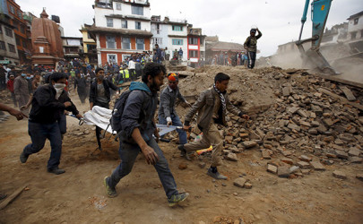 People carry the body of a victim on a stretcher, which was trapped in the debris after an earthquake in Nepal on April 25. (Photo: Navesh Chitrakar /Reuters)