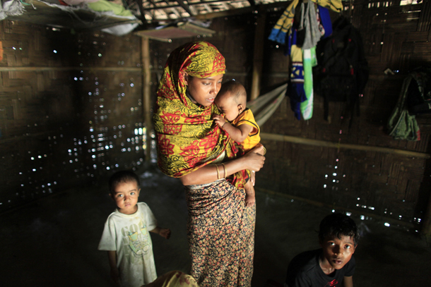 Rohingya refugee Rehana Begum holds her child as she hides in a house in Teknaf, Bangladesh, on June 17, 2012.  (PHOTO: Reuters)