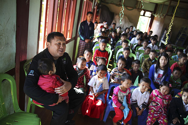 Myanmar tycoon Tay Za holds a child at a school supported by his Htoo Foundation in Myitkyina in 2013. (Photo: Reuters)