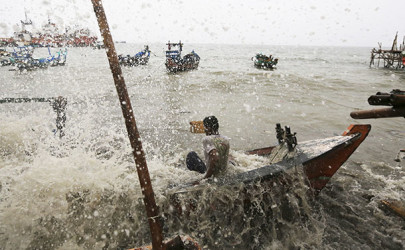 A fisherman falls in his wooden boat as it is hit by strong sea waves, and breaks, in water off the north coast of Jakarta March 10, 2014. (Photo: Reuters)