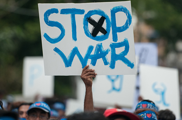 A demonstrator in Rangoon holds up a poster during a march against civil war to mark the International Day of Peace in Sept. 2014. (Photo: Sai Zaw / The Irrawaddy)