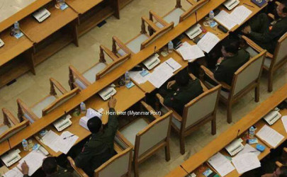 This photo appears to show a military lawmaker voting on behalf of his absent neighbor. (Photo: Hein Htet / Myanmar Post)