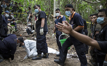 Policemen monitor as forensic experts dig out human remains near the abandoned human trafficking camp in the jungle close the Thailand border at Bukit Wang Burma in northern Malaysia on May 26, 2015. (Photo: Reuters)