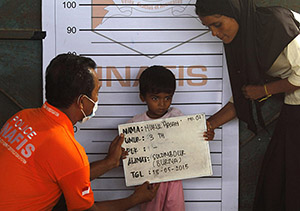 A Rohingya child who recently arrived by boat has his picture taken for identification purposes at a shelter in Kuala Langsa, in Indonesia's Aceh Province, May 18, 2015. The United Nations has called on Southeast Asian nations not to push back the boatloads of Rohingya Muslims from Myanmar and Bangladeshis - men, women and children who fled persecution and poverty at home, and now face sickness and starvation at sea.  REUTERS/Roni Bintang  - RTX1DFBH