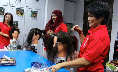 Indonesian domestic workers are pictured during a hairdressing and make-up class at the office of the Transient Workers Count Too charity in Singapore. (Photo: Astrid Zweynert / Thomson Reuters Foundation)