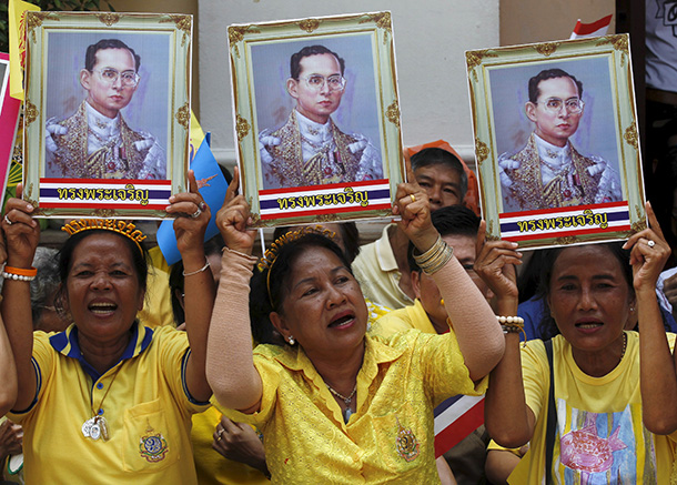 Well-wishers hold up pictures of King Bhumibol Adulyadej at Bangkok's Siriraj Hospital on Sunday. (Photo: Chaiwat Subprasom / Reuters)