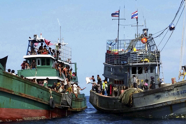 Thai fishermen (R) give some supplies to migrants on a boat drifting 17 km (10 miles) off the coast of the southern island of Koh Lipe, Thailand May 14, 2015. (Photo: Reuters)