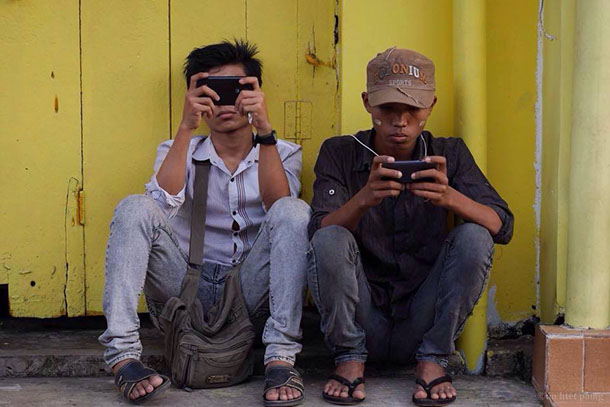 Mobile phone users sit against the side of a building in Rangoon. (Photo: Tin Htet Paing / The Irrawaddy)