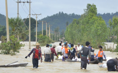 People wade through high waters in Kawlin Township, Sagaing Division, on July 23. (Photo: Teza Hlaing / The Irrawaddy)