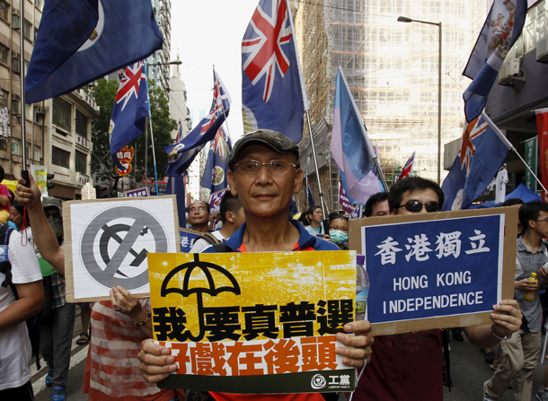 A protester carries a sign reading 'I need real universal suffrage' during a demonstration in Hong Kong, China, on July 1, 2015, marking the 18th anniversary of Hong Kong's handover from British to Chinese sovereignty. (Photo: Reuters)