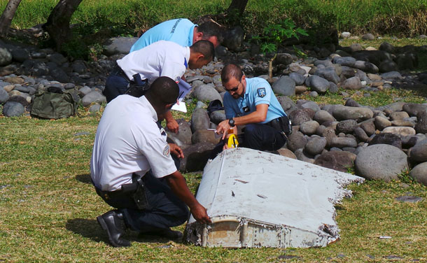 French gendarmes and police inspect a large piece of plane debris which was found on the beach in Saint-Andre, on the French Indian Ocean island of La Reunion, July 29, 2015.