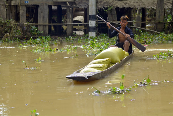 A man steers food relief on a canoe through flood waters in Kawlin Township, Sagaing Division. (Photo: Teza Hlaing / The Irrawaddy)