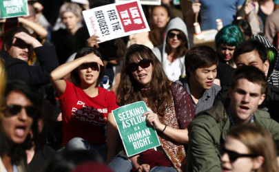 A woman holds a poster during a 2013 rally in support of asylum seekers in central Sydney. (Photo: Daniel Munoz / Reuters)