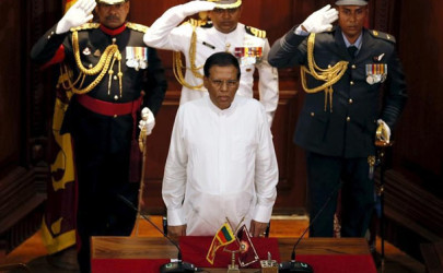 President Maithripala Sirisena, front, stands for the national anthem during a ceremony to swear in Sri Lanka's new prime minister in Colombo, Aug. 21. (Photo: Dinuka Liyanawatte / Reuters)