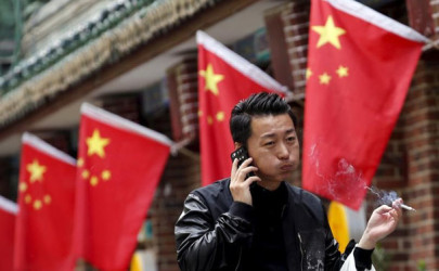 A smoker walks past Chinese national flags in front of a restaurant in Beijing. (Photo: Kim Kyung-Hoon / Reuters)