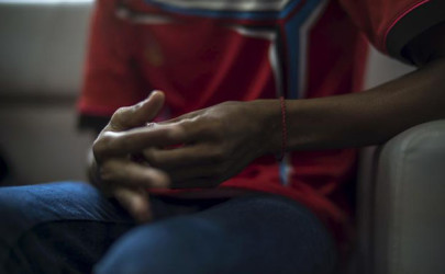 The hands of a Rohingya victim of trafficking are seen as he listens to questions during an interview with the Thomson Reuters Foundation at a temporary shelter in Hat Yai, Songkla, Thailand, September 22, 2015. The strapping 23-year-old Rohingya Muslim was matter-of-fact as he described being forced onto a boat in Myanmar for a tortuous two-month-long journey, beaten and kicked by traffickers as he watched scores die of starvation and thirst along the way.  Picture taken September 22, 2015. To match Thomson Reuters Foundation Feature HEALTH-MENTAL/ROHINGYA       REUTERS/Athit Perawongmetha