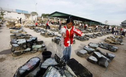 A worker waters jade stones at Burma's 2011 Mid-Year Emporium for jade, gems & pearls at an emporium hall in the capital Naypyidaw, Dec. 24, 2011. (Photo: Reuters)