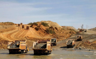 Dump trucks load with soil at a jade mine in Hpakant on Thursday. (Photo: Soe Zeya Tun / Reuters)