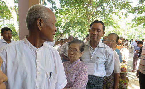 Shwe Mann, third from left, in line at a voting station in Phyu with his wife on Sunday morning. (Photo: Thuzar / The Irrawaddy)